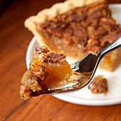 Pecan pie on fork in front of pie slice