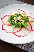 Fresh tuna carpaccio with herb salad and artichokes drizzled with olive oil on a white plate