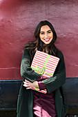 Junge, brünette Frau im Strickmantel hält Geschenkpaket in der Hand