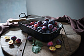 An old roasting pan full of fresh plums