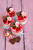 Raspberry mousse decorated with rose petals and heart-shaped biscuits