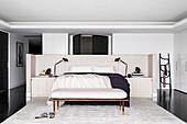 Dopplebett und maßgefertigter Betthaupt mit Ablagefläche, Kleiderbank und Seidenteppich in elegantem Schlafraum