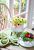 Bouquet of salad leaves and flowers made with cheese, carrots and avocado in a teapot, cress and carrots in a tea cup on a green tablemat