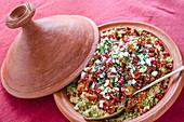 Tajine mit Hähnchen, Couscous, Granatapfelkernen, Feta und Kräutern