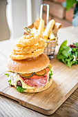 Bacon cheese beef burger with gherkins, pickle, tomato, fresh salad, bacon, cheese and fried onion rings ona wooden board with chips and salad