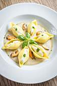 Conchiglioni fresh pasta shells filled with mackerel and ricotta mousse in a creamy white sauce with mussels and pesto sauce