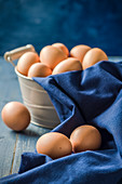 Fresh eggs in a rustic metal basket and blue drape on a blue wooden table and a blue background