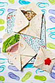Envelopes made with flatbread filled with grilled aubergines and cheese, ham, cheese and salad, and peppers on a colourful background
