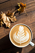 Flat white, cappuccino coffee with rosetta or florette latte art on a wooden background with autumn leaves
