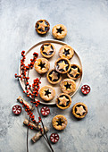 Small Christmas mince pies decorated with berry branches and tealights