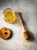 A honey dipper in a puddle of honey, next to open honey jar