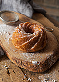 A small bundt cake on a rustic wooden board