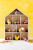 Comical chicks made of chocolate easter eggs in a shelf box