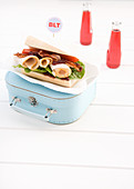 A BLT sandwich with sliced turkey breast on a vintage suitcase