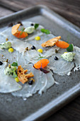 Fish carpaccio with caviar, herb butter, and bread