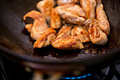 Sautéing chicken in a wok