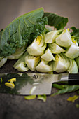 Bok choy cut into quarters, with a knife on a wooden chopping board