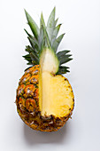 A pineapple on a white surface, with a quarter cut away