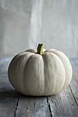 A small white pumpkin on a wooden surface