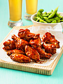 Asian BBQ flavoured chicken wings on a board with edemame and beer.
