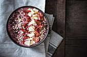 Vegan strawberry smoothie bowl with dried goji berries, mango, quinoa pops and grated chocolate