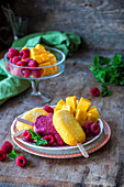 Mango and raspberry ice lollies served with fresh fruit