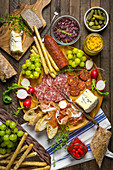 A snack platter with sausages, cheese, bread, grapes and pickles