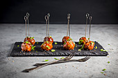 Meatballs with a Hoisin glaze and sesame seeds on skewers