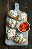 Wholemeal bread with cottage cheese with red radishes and scallion, cherry tomatoes