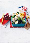 Bento Box mit Avocado-Sesam-Reisbällchen und Joghurt mit exotischen Früchten