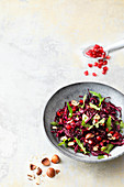Red cabbage salad with rocket, pomegranate seeds and nuts