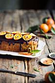 Kastenkuchen mit Schokoglasur und Mandarinenscheiben auf rustikalem Holztisch