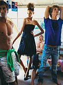 Junge Frau in schwarzem Abendkleid und junge Männer in Badeshort und in zerrisenen Jeans mit T-Shirt