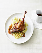 A beer-glazed goose leg on a bed of pointed cabbage