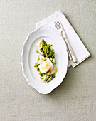 A poached egg on a bed of vegetables with basil foam