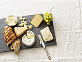 A cheese plate with grapes and a fresh baguette