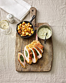 A stuffed pork chop with herb sauce and potato cubes