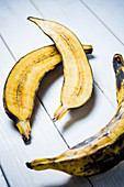 Plantain cut in half and whole on a white wooden background