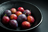 bowl of fresh purple and red prunes and plums in a black fruit bowl on a black background