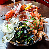 Fresh seafood platter with red lobster, langoustine, prawns, mussels, oysters, clams, with a tartare and sweet chilli sauce
