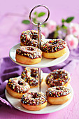 Mini doughnuts with icing and sugar strands on a cake stand