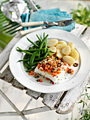 A cod fillet topped with vegetables and served with green beans and potatoes
