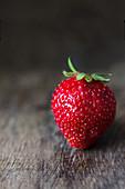 Frische Erdbeere auf dunkler Holzoberfläche