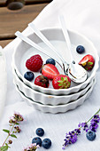 Various berries in a stack of porcelain bowls with spoons and meadow flowers