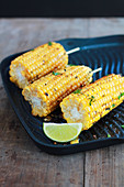 Grilled corn on the cob with chopped coriander in a grill pan with lime wedges