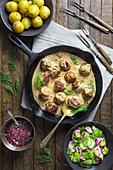 Swedish meatballs in a creamy sauce with cucumber salad and new potatoes