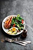 A mixed salad with a fried egg and roasted sweet potatoes