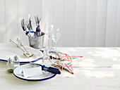 A table laid with salt and pepper shakers and cutlery in a champagne bucket