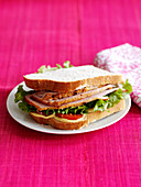 A sandwich with ham and salad