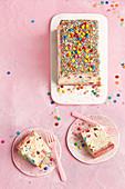 Tutti-Frutti-Eistorte in Kastenform verziert mit Zuckerstreuseln und Schokolinsen